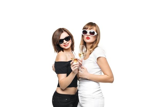 High-fashion. glamouröses stilvolles junges frauenmodell mit roten lippen in einer schwarzen und weißen hellen hipster-kleidung und einer sonnenbrille mit gläsern champagner
