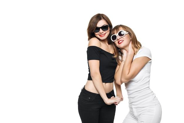 High-fashion. glamouröses stilvolles junges frauenmodell mit roten lippen in einer schwarzen und weißen hellen hipster-kleidung und einer sonnenbrille. sie lachen, freuen sich, toben, gönnen sich etwas