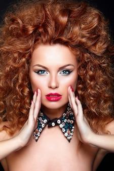 High fashion look.glamour nahaufnahme porträt der schönen sexy rothaarigen kaukasischen jungen frau modell mit roten lippen, helles make-up, mit perfekter sauberer haut mit schmuck auf schwarz isoliert
