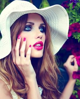 High fashion look. glamour nahaufnahme porträt des schönen sexy stilvollen blonden jungen frau modell mit hellem make-up und rosa lippen mit perfekter sauberer haut in hut blauen augen