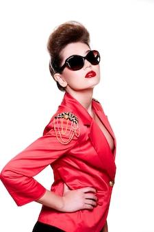 High fashion look. glamour-nahaufnahmeporträt der sexy brünetten kaukasischen jungen weiblichen frau mit hellem make-up mit roten lippen in der leuchtend rosa jacke in der sonnenbrille