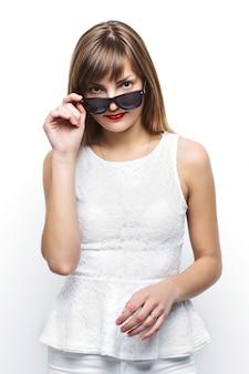 High fashion look.glamour stilvoll schönes junges weibliches modell mit roten lippen in weißen sommer hellen bunten stoff und hipster sonnenbrille.