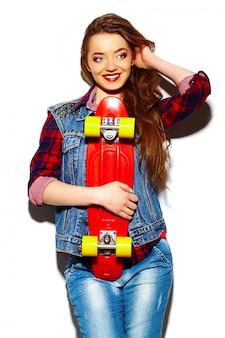 High fashion look. glamouröses stilvolles schönes junges brünettes frauenmodell im sommerhellen hipster-stoff mit skateboard