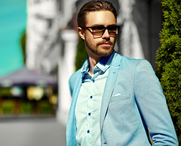 High fashion look. junges stilvolles, selbstbewusstes, glückliches, gutaussehendes geschäftsmannmodell im anzug auf der straße mit sonnenbrille