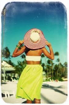 High fashion look. rückseite des glamourösen sexy modellmädchens im retro-stil mit palmen in buntem stoff und sonnenhut hinter blauem strandhimmel