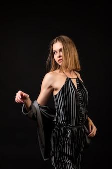 High fashion model frau im schwarzen overall und strickjacke auf schwarz
