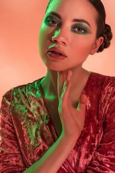 High fashion model frau in bunten hellen lichtern posiert im studio,