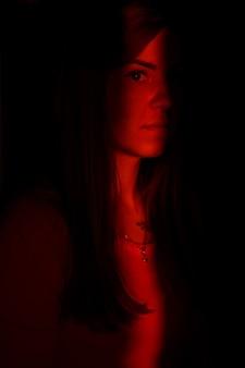 High fashion model im lichtstrahl im dunkeln. glamour sexy girl kreatives modisches portrait. gerichteter lichtstrahl auf das weibliche gesicht