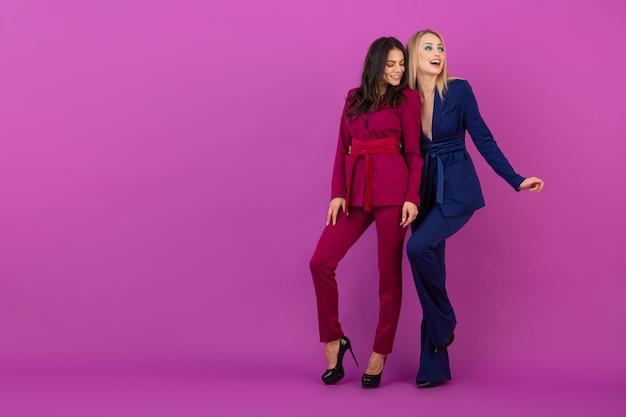 High fashion style zwei lächelnde attraktive frauen auf violetter wand in stilvollen bunten abendanzügen von lila und blauer farbe, freunde, die spaß zusammen haben, modetrend