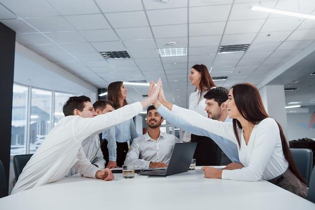 High five alle. arbeit ist erledigt. gruppe von büroangestellten, die glücklich sind, ihre eigenen rekorde zu schlagen und erfolgreich zu sein