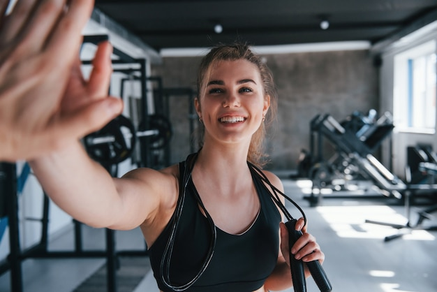 High-five geben. wunderschöne blonde frau im fitnessstudio zu ihrer wochenendzeit