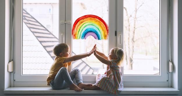 High five kleine kinder auf dem hintergrund der malerei regenbogen am fenster