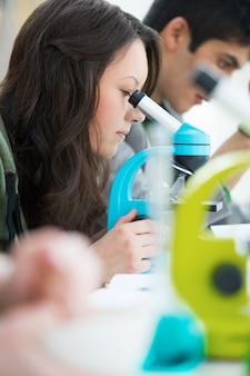 High-school schüler. junge hübsche studentin, die durch mikroskop im wissenschaftsklassenzimmer blickt