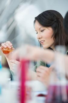 High-school schüler. mischende reagenzien des hübschen weiblichen studenten, die glaswaren in der klassenzimmerumgebung verwenden