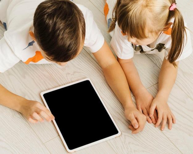 High view geschwister mit einem digitalen tablet