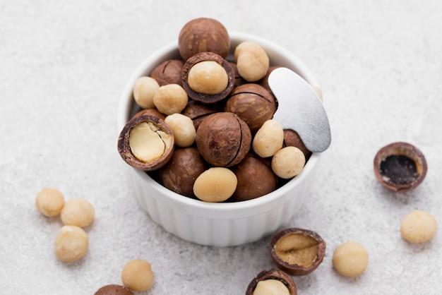 High view köstliche schüssel mit macadamia-nüssen in schokoladenröllchen