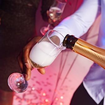 High view männchen, das champagner in ein glas gießt
