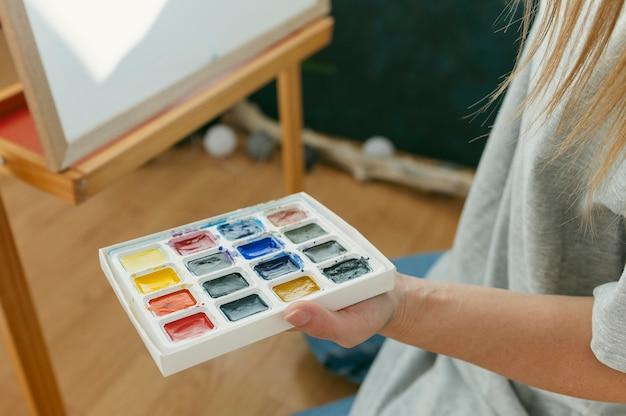 High view maler hält ihre farbpalette
