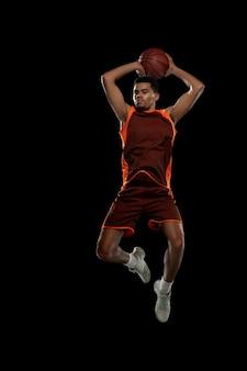 High young zielgerichteter afrikanisch-amerikanischer basketballspieler, der in aktion übt