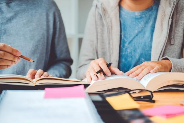 Highschool oder collegestudenten, die zusammen in der bibliothek studieren und lesen