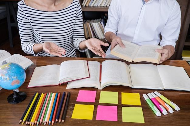 Highschool- oder student-gruppe, die am schreibtisch in der studierenden und lesenden bibliothek sitzt, hausaufgaben macht und lektion üben