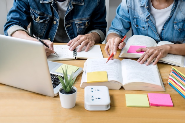 Highschool tutor- oder student-gruppe, die am schreibtisch in der studierenden und lesenden bibliothek sitzt