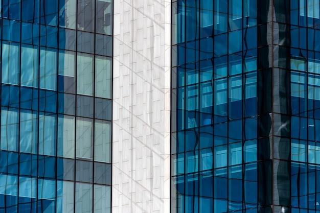 Hightech-bürogebäude mit transparenten wänden, die einen strahlend blauen himmel mit wolken widerspiegeln. moderne architektur. abstrakter glashintergrund