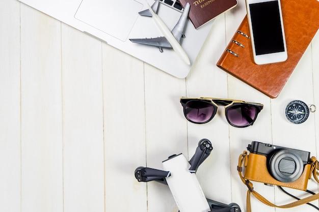 Hightech-reisegegenstände und -geräte für modernen reisenden mit weißem hölzernem kopienraum