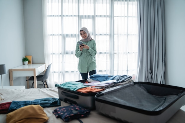 Hijab frau, die abflugpläne über smartphone-app überprüft