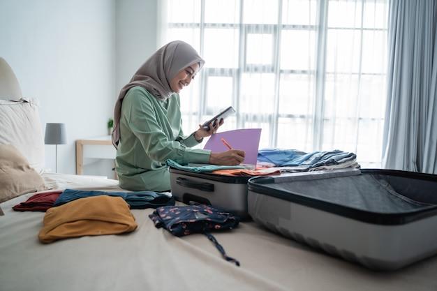 Hijab frau, die auf dem bett sitzt, während sie die liste der gegenstände betrachtet