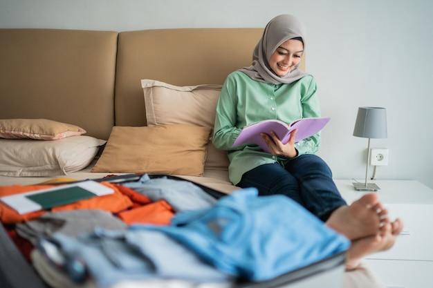 Hijab frau, die auf dem bett sitzt, während sie ein buch betrachtet