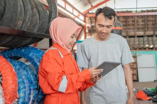 Hijab-frauen in wearpack-uniformen verwenden digitale tablets, um den verbrauchern in werkstätten den reifentyp zu zeigen