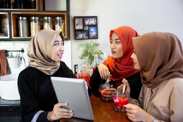 Hijab-frauen und -freunde, die digitale tablets verwenden, während sie darauf warten, ihr fasten zu brechen