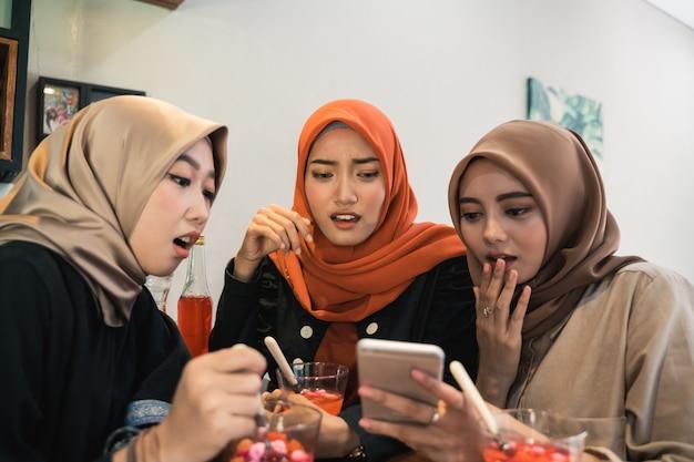Hijab frauen und freunde schauen sich videos auf einem smartphone an und sind geschockt