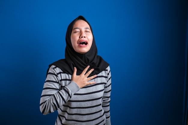 Hijab muslimisches mädchen ist depressiv und traurig, sie weint, sie schließt ihre augen und hält ihre brust und fühlt den schmerz