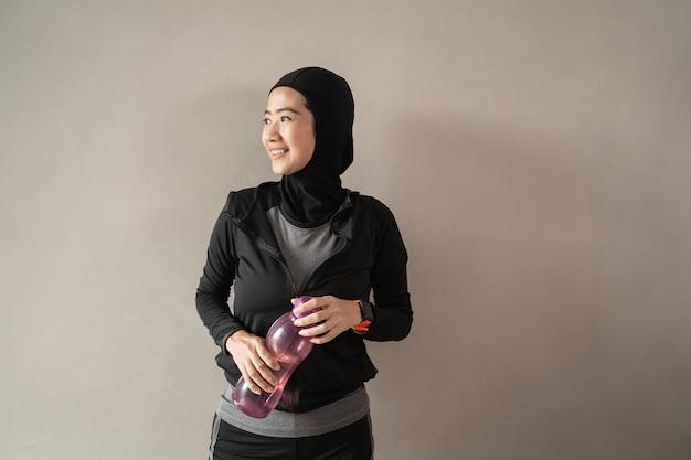 Hijab sportliche asiatische damen, die sportbekleidung tragen, halten eine flasche