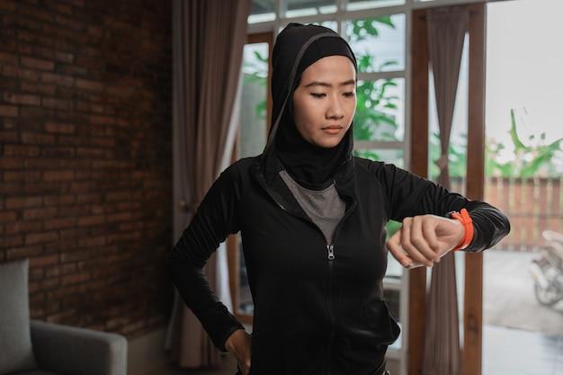 Hijab sportliche asiatische damen schauen auf das smarte armband, um die zeit einzustellen