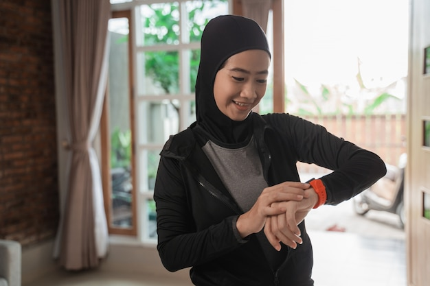 Hijab sportliche asiatische frau, die ein intelligentes armband betrachtet, um die zeit einzustellen