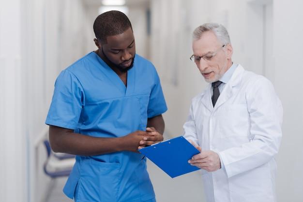 Hilfe für die junge generation. alter qualifizierter freundlicher arzt, der im krankenhaus steht, ordner hält und afroamerikanerpraktikanten konsultiert