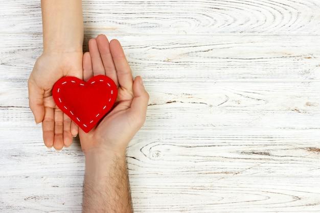 Hilfe, herz in der hand auf hölzernem hintergrund. valentinstag-konzept. kopieren sie platz