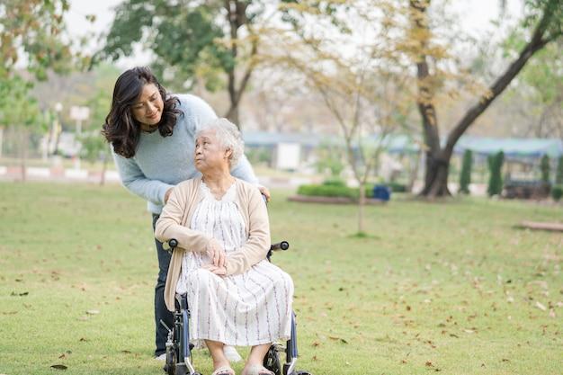 Hilfe und pflege asiatische ältere patientin, die auf rollstuhl im park sitzt.