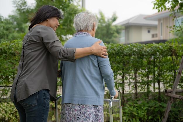 Hilfe und pflege asiatische senioren oder ältere alte damen verwenden einen walker mit starker gesundheit, während sie im park in einem glücklichen, frischen urlaub spazieren gehen.
