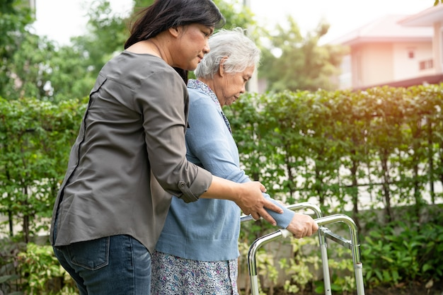 Hilfe und pflege asiatische senioren oder ältere alte damen verwenden einen walker mit starker gesundheit, während sie im park in einem glücklichen frischen urlaub spazieren