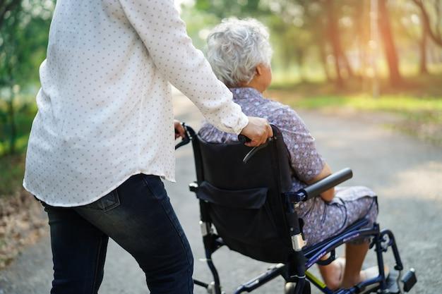 Hilfe und sorgfalt asiatischer älterer oder älterer frauenpatient alter dame, der auf rollstuhl sitzt