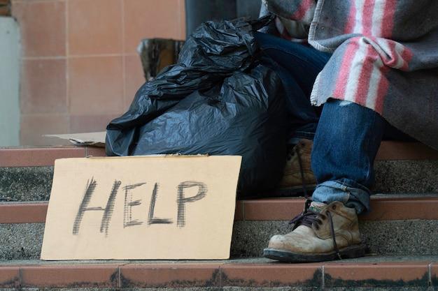 Hilfezeichen von einem obdachlosen, der am straßenrand sitzt.