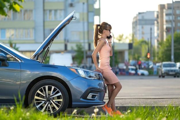 Hilflose frau, die in der nähe ihres autos mit offener motorhaube steht und den straßendienst um hilfe ruft. junge fahrerin, die probleme mit dem fahrzeug hat.
