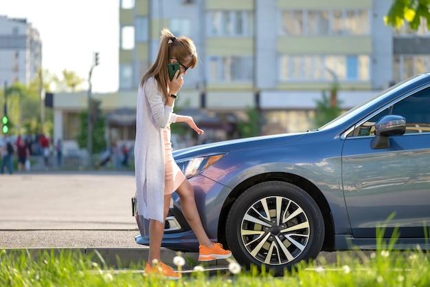 Hilflose frau, die in der nähe ihres kaputten autos steht und den straßendienst um hilfe ruft. junge fahrerin, die probleme mit dem fahrzeug hat.