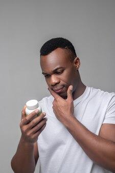 Hilfreiche information. interessierter denkender dunkelhäutiger mann in hellem t-shirt, der gut gelaunt auf vitaminpaket schaut