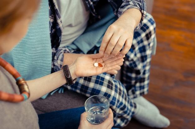 Hilfreiche medizin. draufsicht auf pillen, die auf der handfläche liegen, während sie einem kranken reifen mann gegeben werden