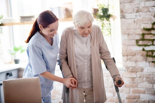 Hilfreiche niedliche pflegekraft, die frau mit krücken hilft